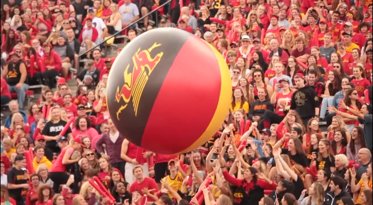 A large ball moving through the crowd at homecoming.