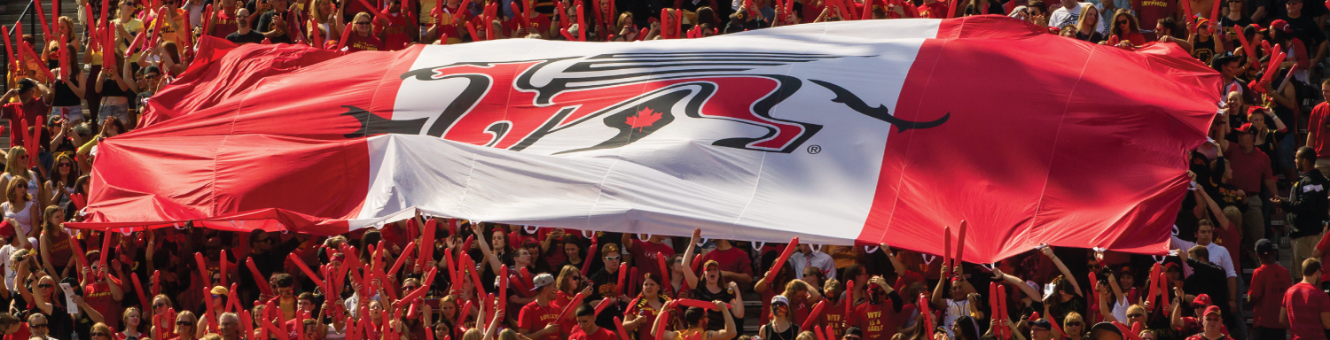 A crowd at the Football Stadium holding a large Gryphon Flag.