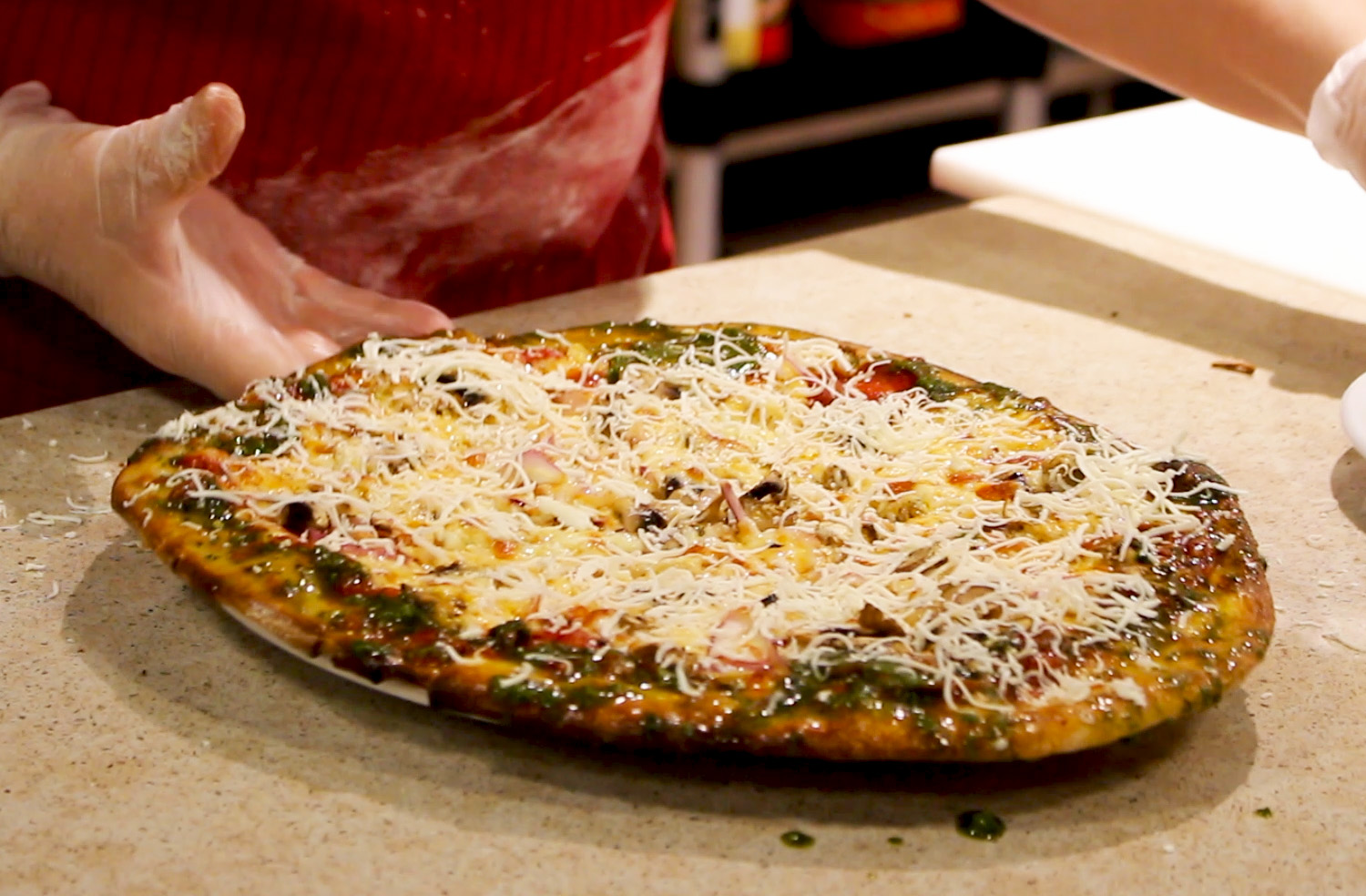 Pizza with fresh parmesan cheese and pesto on the crust.