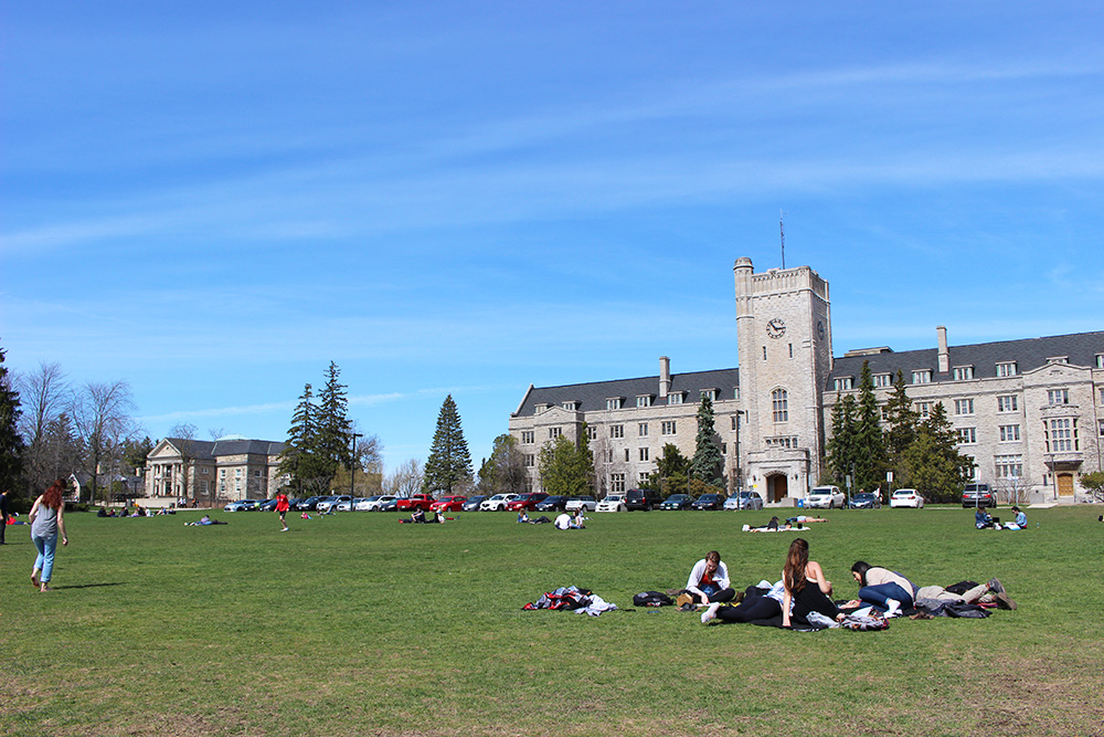 Students laying on Johnston Green in the sun.