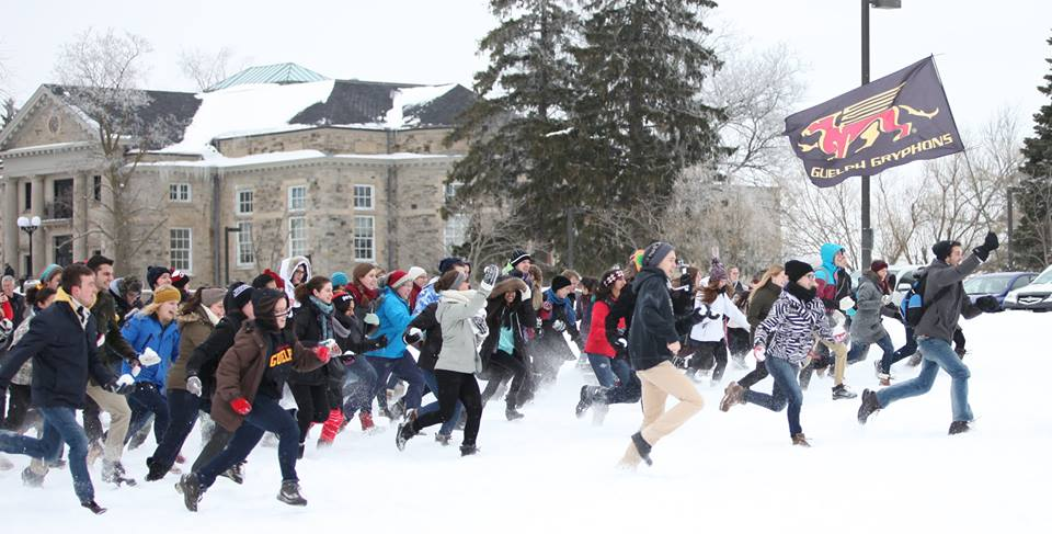 A group of students running in the snow, holding snow balls, preparing for a snow ball fight. The student in the front is running with a Gryphon flag.