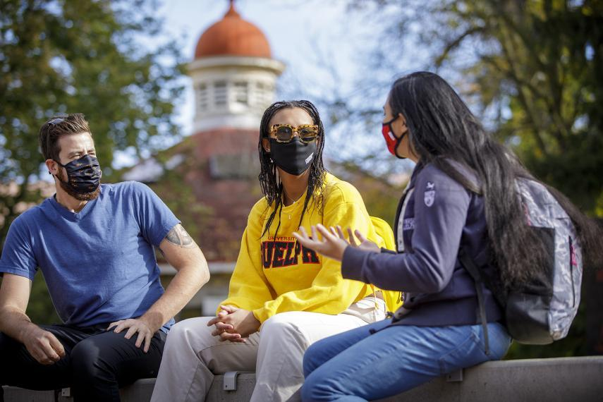 Three students wearing masks conversing outdoors on campus.