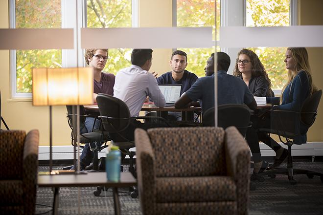 Six students working together in the Gordon S. Lang School of Business
