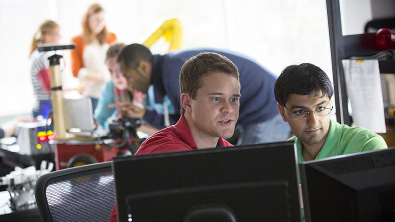 Two men at a computer while engineering students work on a robot in the background