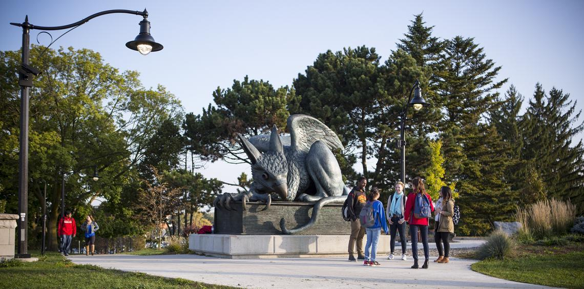 Students standing by the Gryphon statue