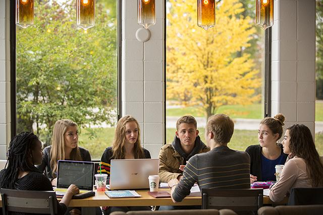 Seven students sit together at a table in the library