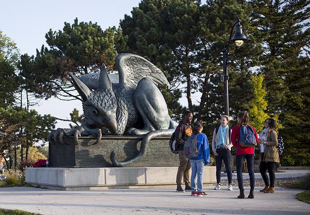 Five students conversing next to the Gryphon statue.