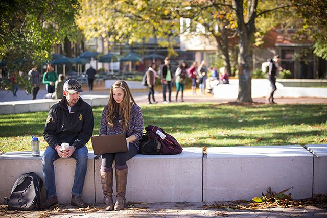 Two students sitting outside looking at a laptop