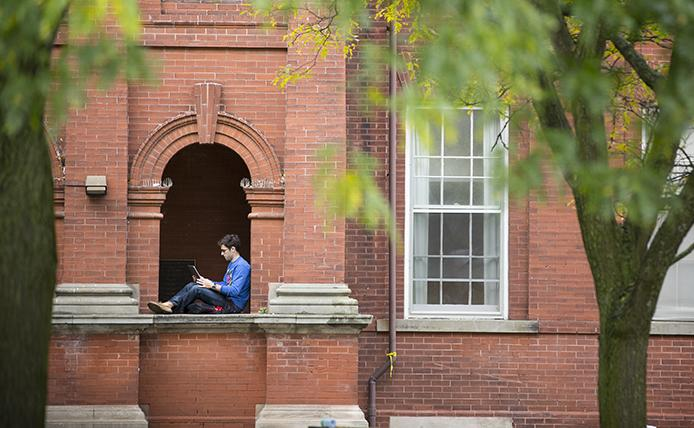 A U of G student with his laptop in a comfy nook on campus.